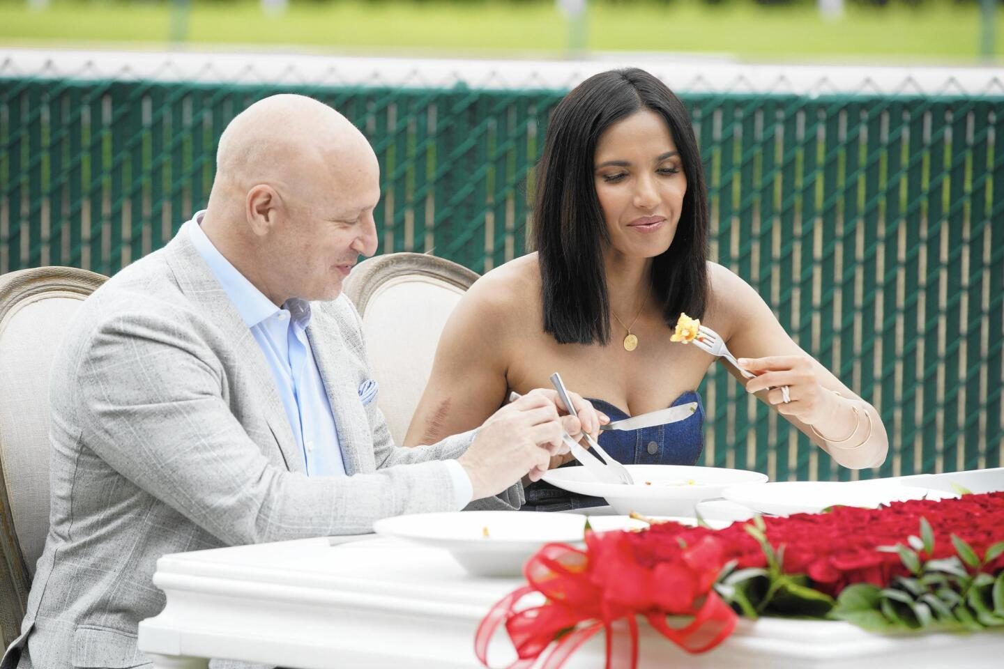 """""""Top Chef"""" head judge Tom Colicchio and host Padma Lakshmi dig into contestants' food at Churchill Downs in the season premiere of the Bravo cooking competition, airing Dec. 6."""