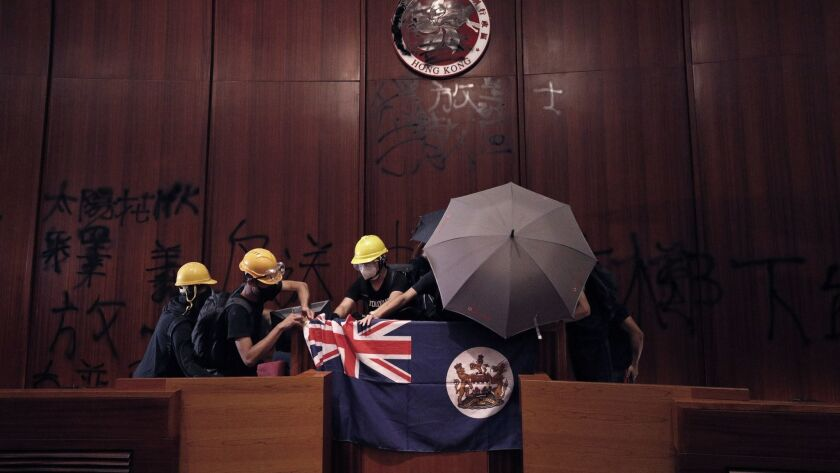 FILE - In this July 1, 2019, file photo, protesters put a Hong Kong colonial flag and deface the Hon