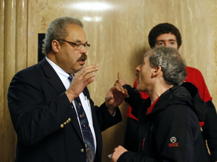 Rep. Lew Frederick, D-Portland, left, talks with Guy Berliner during a protest march in the Capitol Building, in Salem , Ore., on Thursday, Feb. 18, 2016. The group is protesting for a higher minimum wage, local control of rent control laws, and an end to Oregon Department of Transportation sweeps