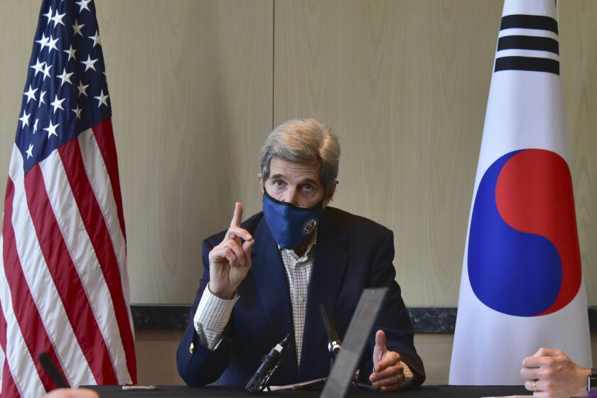 John Kerry raises his finger while sitting between a U.S. and South Korean flag.
