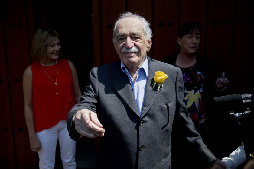 Gabriel García Márquez, con traje azul y chaqueta amarillo-rosa con solapa, sonriendo y apuntando a la cámara
