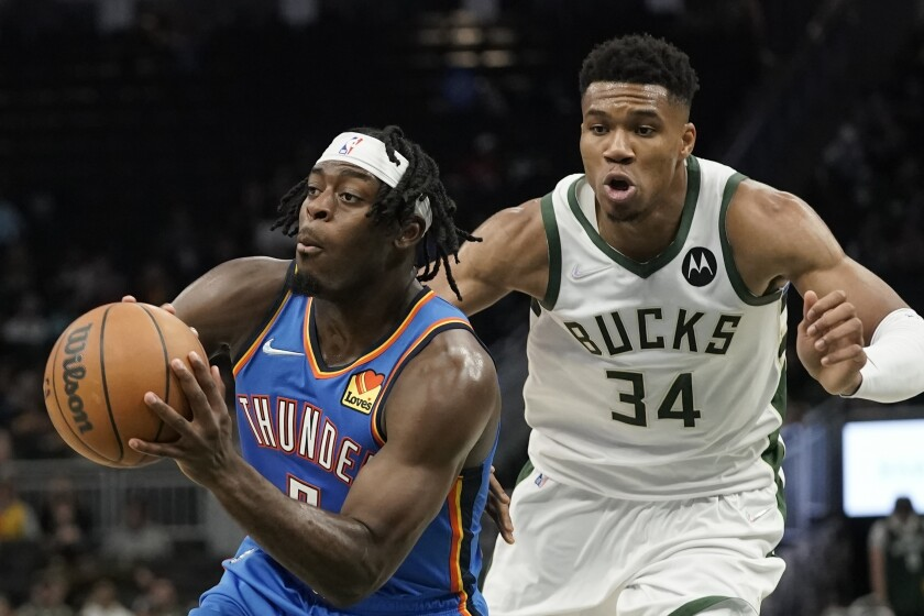 Oklahoma City Thunder's Luguentz Dort looks to pass in front of Milwaukee Bucks' Giannis Antetokounmpo during the first half of an NBA preseason basketball game Sunday, Oct. 10, 2021, in Milwaukee. (AP Photo/Morry Gash)