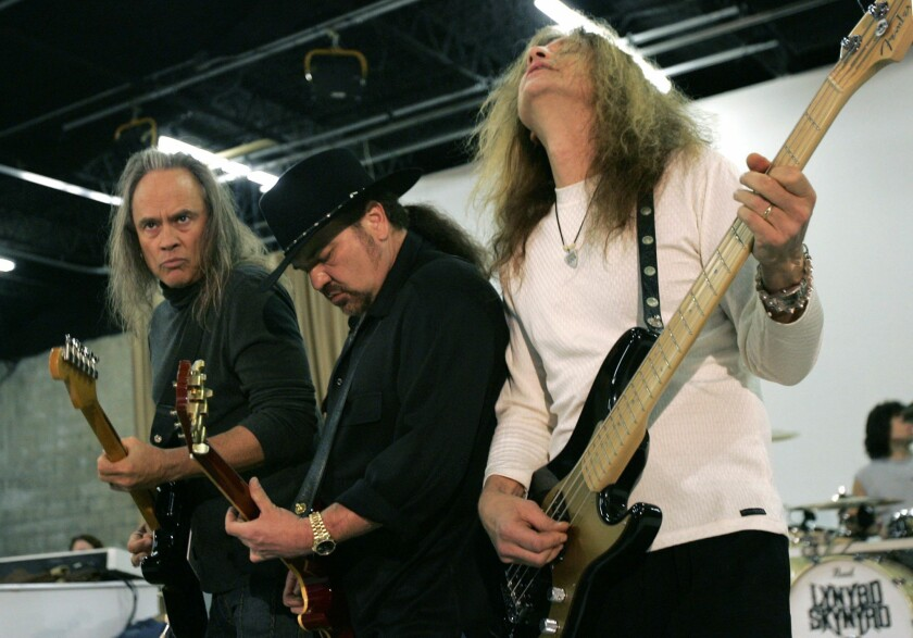 FILE - In this Friday, Feb. 4, 2005 file photo, Members of Lynyrd Skynyrd, from left, Rickey Medlocke, Gary Rossington and Ean Evans, practice at the Jacksonville Production Studio in Jacksonville, Fla. for their Saturday performance as part of the Super Bowl concert series. Lynyrd Skynyrd has pulled out of the Pro Football Hall of Fame concert after guitarist Rickey Medlocke tested positive for COVID-19, Saturday, Aug. 7, 2021. The band was set to co-headline the concert Monday night with Brad Paisley. According to a band statement, Medlocke's positive test forced the group's withdrawal. (AP Photo/Ann Heisenfelt, File)