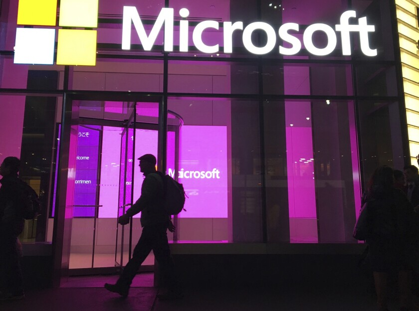 FILE - In this Nov. 10, 2016, file photo, people walk past a Microsoft office in New York. Microsoft on Oct. 7, 2021, says Russia once again accounted for most state-sponsored hacking, with a 58% share of intrusion attempts it detected in the past year. The targets were mostly government agencies — in the United States, followed by Ukraine, Britain and European NATO members. (AP Photo/Swayne B. Hall, File)