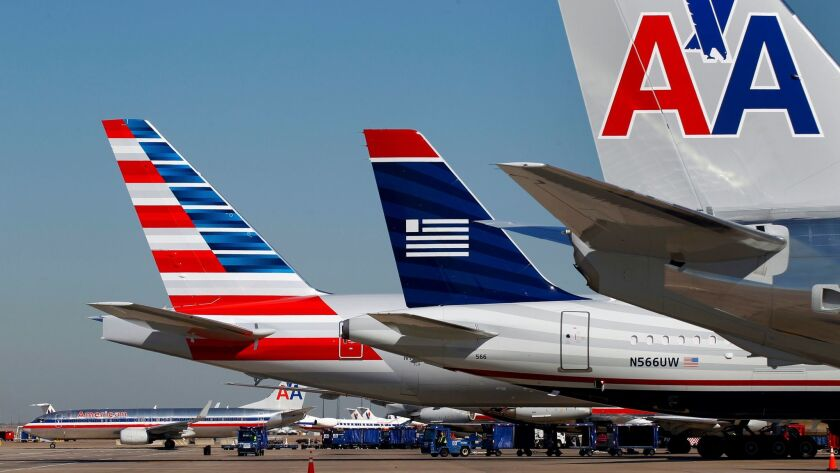 A US Airways plane is parked between two American Airlines planes, one bearing the new logo, (far le