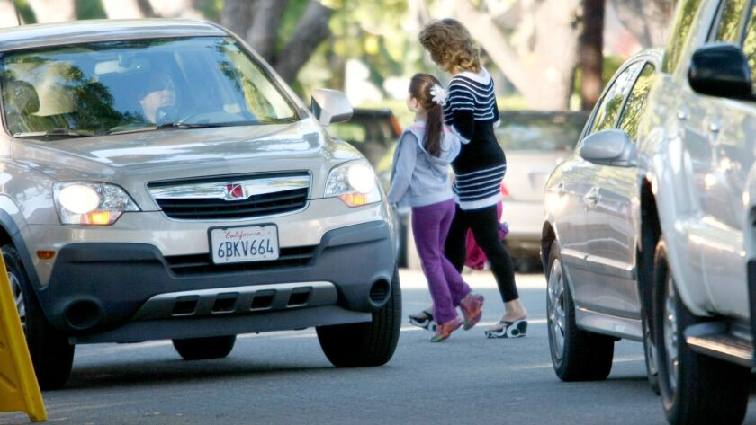 A woman crosses with a child in the middle of traffic on Allen south of Bel Aire Dr. in front of Balboa Elementary School in Glendale in April 2014.