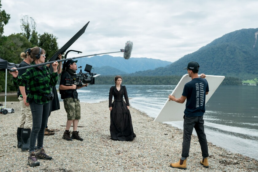 A woman in a black dress by the water, surrounded by a film crew.