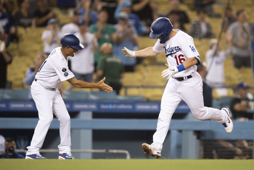 Will Smith (derecha), de los Dodgers de Los Ángeles, celebra un jonrón de dos carreras con el entrenador de tercera base Dino Ebel durante el cuarto inning del juego de la MLB que enfrentó a su equipo con los Filis de Filadelfia, el 14 de junio de 2021 en Los Ángeles. (AP Foto/Kyusung Gong)