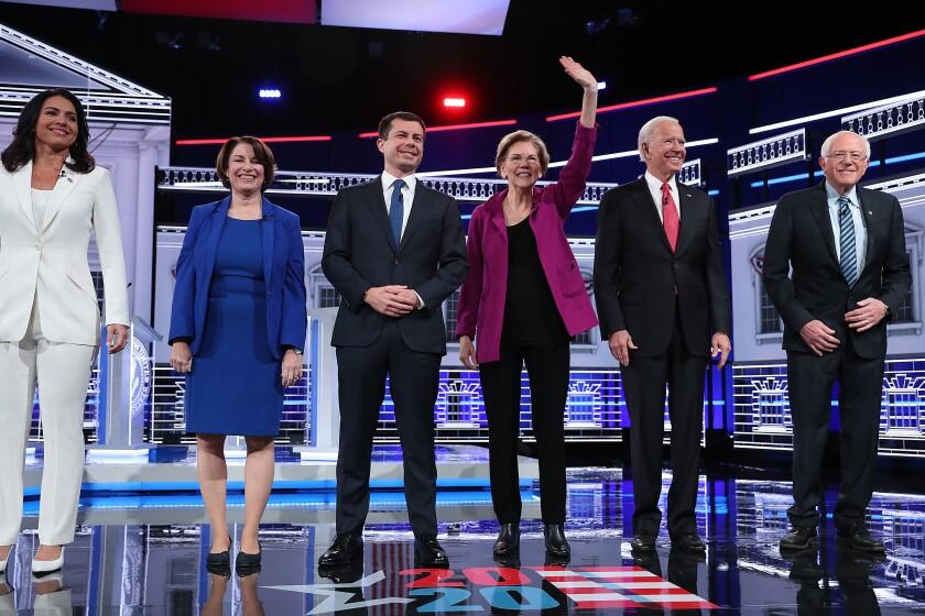 Democratic presidential candidates, from left, Tulsi Gabbard, Amy Klobuchar, Pete Buttigieg, Elizabeth Warren, Joe Biden and Bernie Sanders, arrive on stage before the start of their debate in Atlanta on Wednesday.
