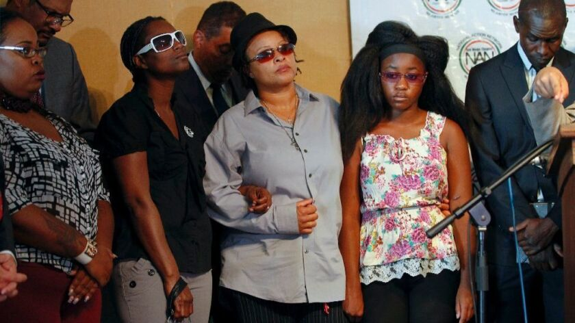 Alfred Olango's widow, Taina Rozier, center, and 16-year-old daughter, second from right, appear at news conference in San Diego on Thursday. Olango was killed by police in September.