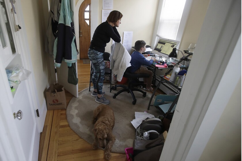 Rebecca Biernat watches as her 6-year-old son, Seamus, takes a live class online at their home in San Francisco.