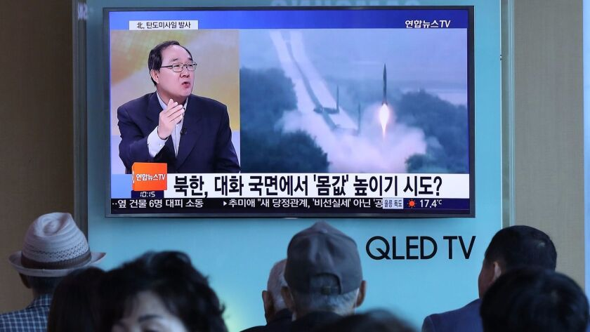 People watch a television news programme, showing file footage of a North Korean missile launch, at