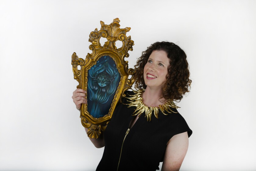 """Sonya Sparks, owner and curator of Sparks Gallery in San Diego, holds an acrylic painting by artist Gloria Muriel, titled """"€œThought Garden""""€ and is wearing a gold leaf necklace by Alexandra Hart."""
