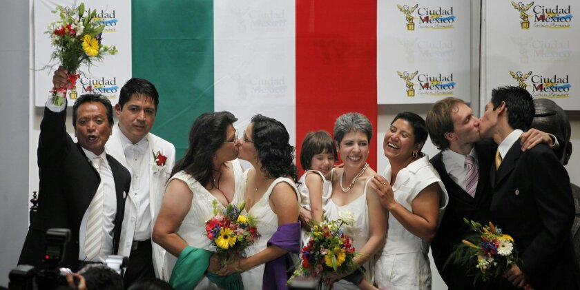 FILE - In this March 11, 2010 file photo, same sex couples celebrate after getting married at City Hall in Mexico City. The couples wed under Latin America's first law that explicitly approves gay marriage. Mexican President Enrique Pena Nieto on Tuesday, May 17, 2016, proposed legalizing gay marri