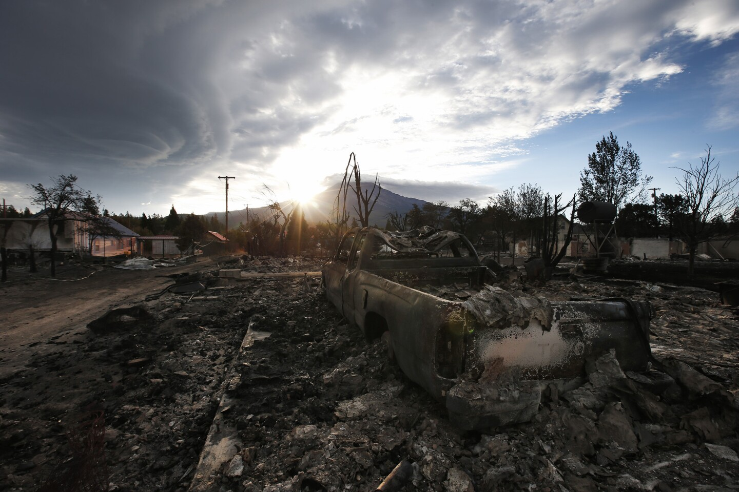 The sun rises behind Mt. Shasta overlooking the devastated Angel Valley neighborhood two days after the Boles Fire, pushed by heavy winds devastated this town near the California and Oregon border.