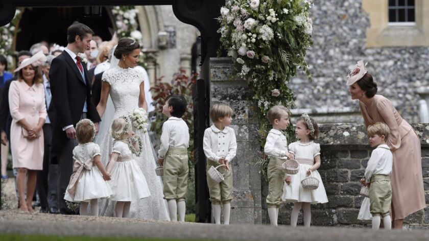 Kate, Duchess of Cambridge, right, stands with her son Prince George as she looks across at Pippa Mi
