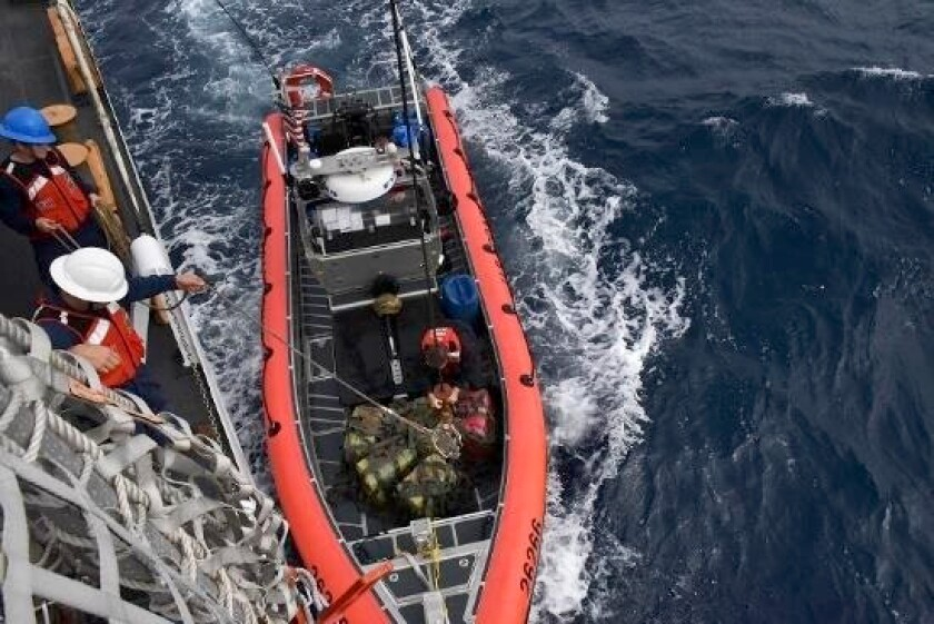 In this Nov. 16, 2019 photo provided by the U.S Coast Guard, crew members from the cutter Thetis hoist interdicted drugs seized in international waters of the Eastern Pacific Ocean. The U.S. Coast Guard says nearly 20,000 pounds of cocaine seized in the eastern Pacific Ocean has been brought to San Diego. The drug haul estimated to be worth about $338 million is scheduled for off loading from the cutter Munro at Naval Base San Diego on Monday morning, Feb. 10, 2020. The cocaine was seized in eight operations by the crews of four cutters between mid-November and mid-January. (Petty Officer 1st Class Mark Barney/U.S. Coast Guard via AP)