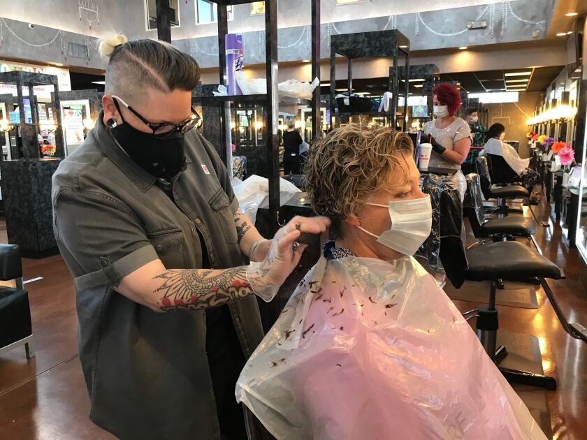 Natascha Updegrove, a stylist at Three-13 Salon, Spa and Boutique, cuts Karon Gilmore's hair on the first day that Georgia reopened salons, spas, gyms and bowling alleys.