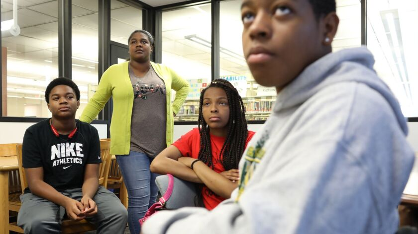 Khallilah Beecham-Watkins, 28, standing, counsels a group of teen students on Aug. 9, 2018, during a meeting of Upward Bound at the Carter G. Woodson Library on the South Side. She was giving a presentation on paying for college.