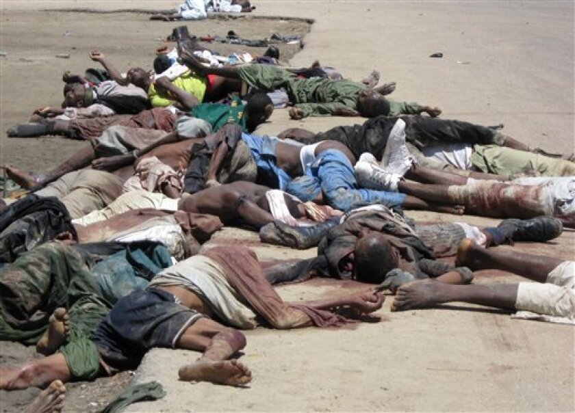 In this image taken on Monday, July 27, 2009 in Maiduguri, Nigeria, bodies lie in the street in front of police headquarters following clashes with police. Nigerian authorities imposed curfews and poured security forces onto the streets of several northern towns on Tuesday, July 28, 2009, after a t