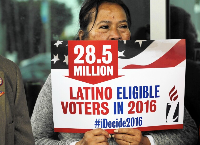 Georgina Arcienegas holds a sign in support of Latino voters during a protest outside the office of Florida Rep. Carlos Trujillo, Tuesday, Jan. 12, 2016, in Doral, Fla.