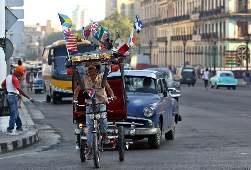 Un bicitaxi adornado con varias banderas, entre ellas una de EE.UU., circula por una calle de La Habana, la capital cubana.