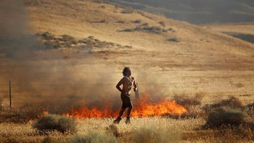 A man suspected of starting fires in Neenach is seen running away from flames.