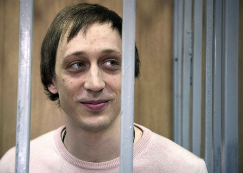 FILE - In this Tuesday Dec. 3, 2013 file photo, Pavel Dmitrichenko stands inside a barred enclosure at a courtroom in Moscow, Russia. A Bolshoi dancer who was convicted in 2013 for his role in an acid attack on the ballet's artistic director has been paroled. Russian news agencies on Wednesday, Jun
