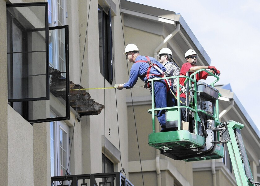 Crew members measure the remaining wood from a balcony that collapsed from the fifth floor of the Library Gardens apartment complex in Berkeley.