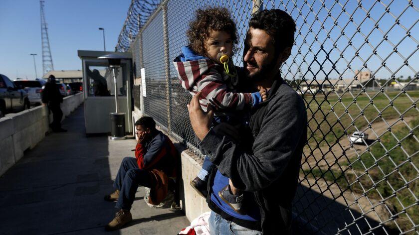 Political asylum seekers Elvis Gonzalez, 23, left, a Cuban from Havana, and Brazilians Robert Richard Braganca of Rio de Janeiro and son Mario, 18-months, camp out on the Matamoros and Brownsville International Bridge in Matamoros, Mexico.