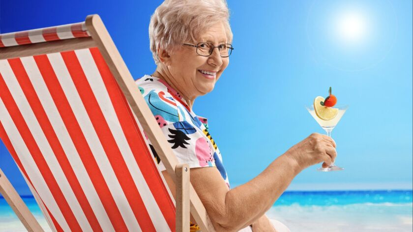 Elderly woman with a cocktail sitting in a deck chair