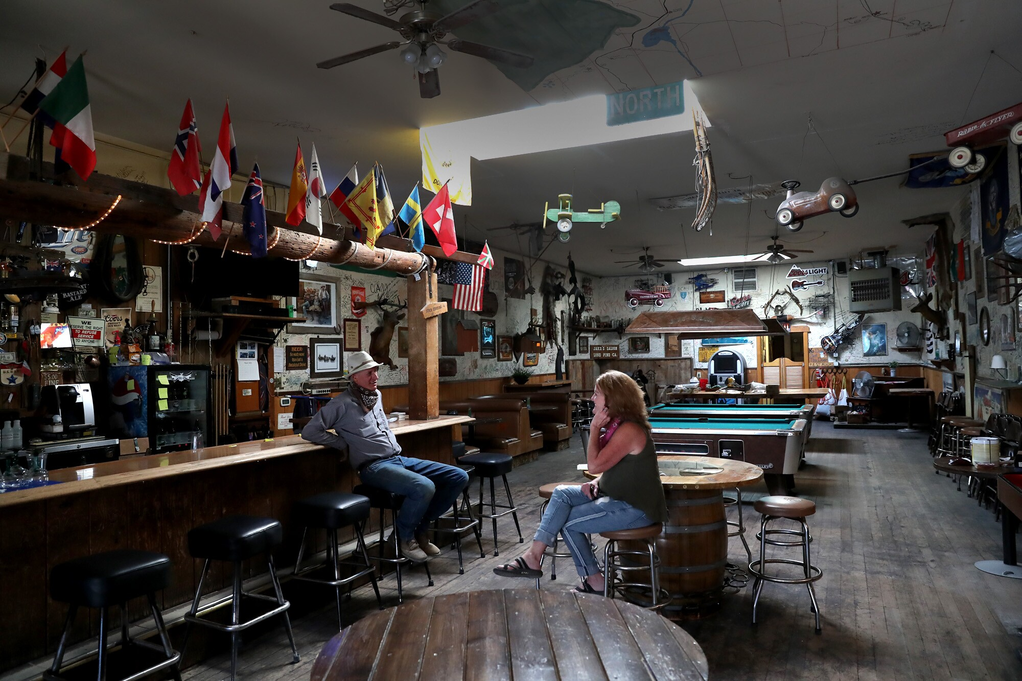 Jake's Saloon owners Sherri Newman and Forrest Newman chat inside the Lone Pine, Calif., bar. To help make ends meet during the shutdown, Newman and her workers removed dollar-bill tips that had been stapled to the walls over the years.