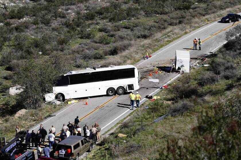 Investigators look over the scene where a tour bus crashed on California Highway 38 near Yucaipa. Seven people were killed. The U.S. Department of Transportation is cracking down on unsafe bus companies.