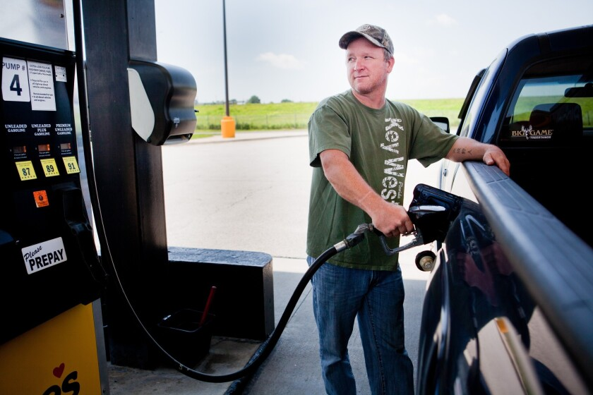 Lance Thompson pumps gas into his truck at a Love's station in St. Joseph, Mo., last month.