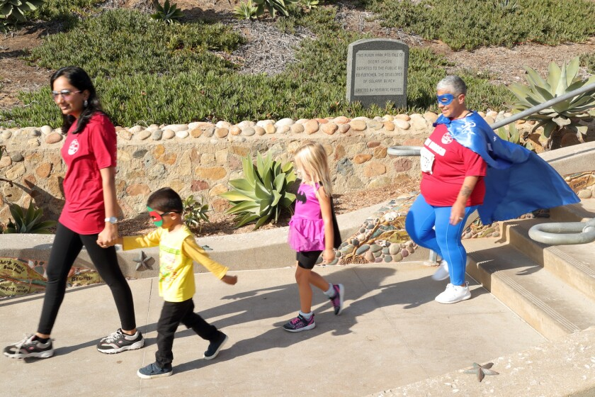 Participants in the SuperHero costume contest make their way to the stage