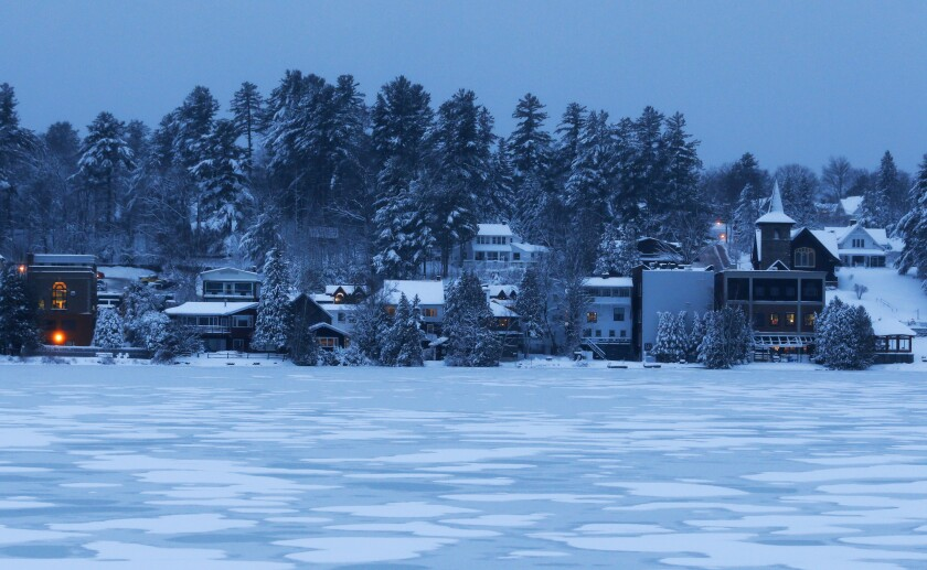 In this Thursday, Dec. 11, 2014 file photo, night falls over the homes and condominiums on the banks of Mirror Lake in Lake Placid, N.Y. The surge in the number of short-term rentals in this Adirondack Mountain resort is alarming local residents who fear it is changing the character of the village. (AP Photo/Mike Groll)