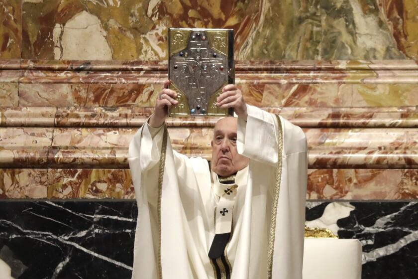 El Papa Francisco sostiene un libro sagrado durante una misa de Jueves Santo en la Basílica de San Pedro