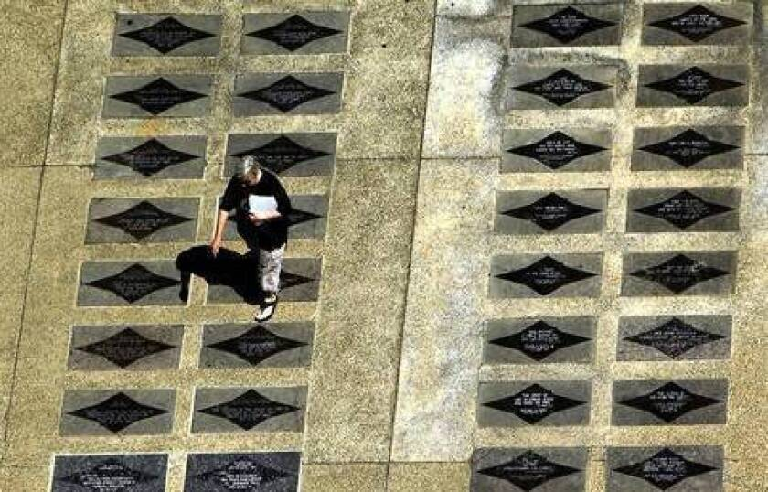 A visitor strolls the Walk Of Faith on the grounds of the former Crystal Cathedral in Garden Grove. The 1,800 steppingstones that make up the walk are being removed as part of the property's $53-million renovation.