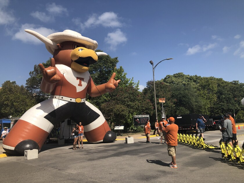 A man takes a picture of two people in front of a giant inflatable Longhorn on the street