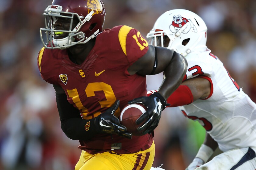 Former USC tight end Bryce Dixon is suspected of participating in a two-day string of robberies, which included a carjacking, in L.A. and Ventura counties, police say.
