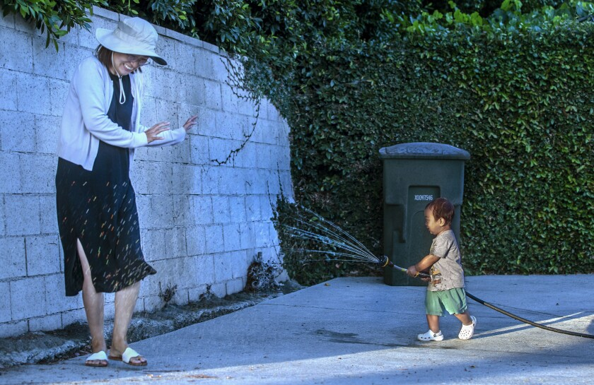 Ian Choi, 21 months old, aims a hose at his mother Younkyung Ko, while playing in front of their home.