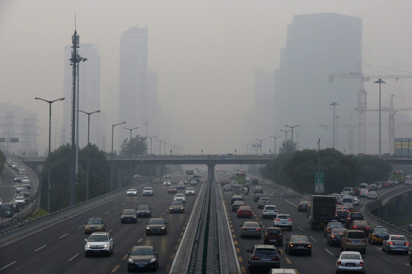 Vehicles travel a main thoroughfare while the Air Quality Index reaches risky levels in Beijing.