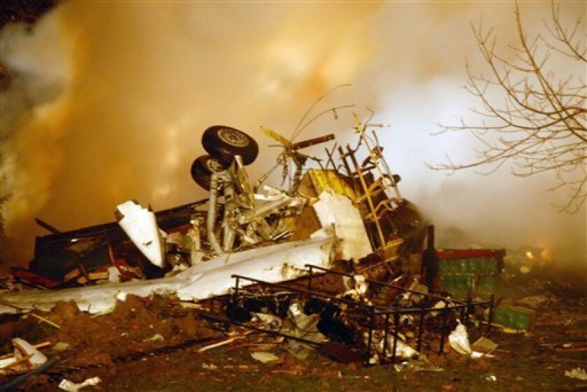 The wreckage of Continental flight 3407 lies amid smoke after crashing into a suburban Buffalo home and erupting into flames late Thursday Feb. 12, 2009, killing all 48 people aboard and at least one person on the ground, according to authorities. The 74-seat Q400 Bombardier aircraft, operated by Colgan Air, was flying from Newark Liberty International Airport in New Jersey to Buffalo Niagara International Airport (AP Photo/Dave Sherman)