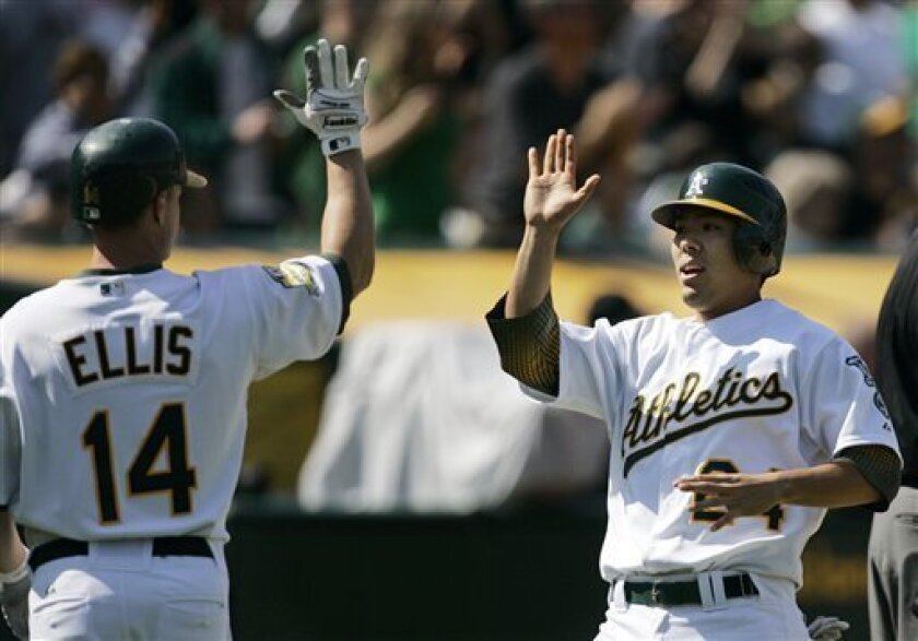 Oakland Athletics' Kurt Suzuki, right, is congratulated by teammate Mark Ellis after scoring against the Kansas City Royals in the seventh inning of a baseball game Saturday, April 19, 2008, in Oakland, Calif. Suzuki scored on a triple by Daric Barton. (AP Photo/Ben Margot)