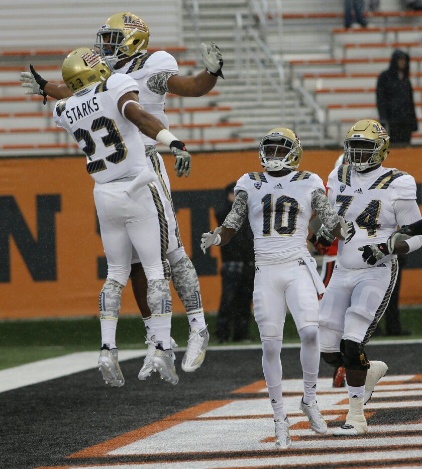 UCLA's Nate Starks, left, celebrates with teammates after scoring a touchdown in the second half of an NCAA football game, in Corvallis, Ore., on Saturday, Nov. 7, 2015. (AP Photo/Timothy J. Gonzalez)