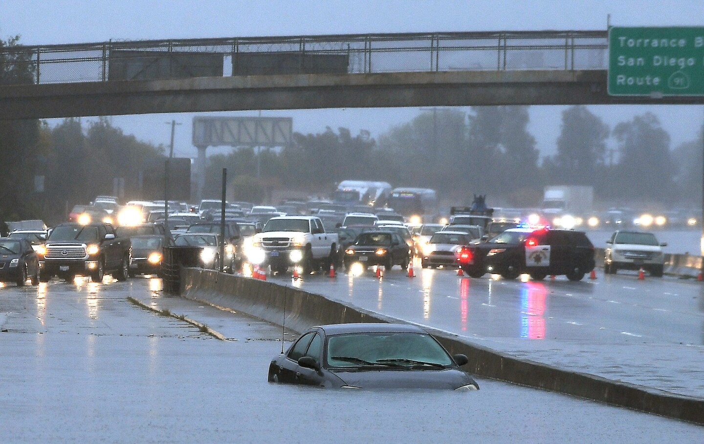 A car is stuck in standing water on the southbound 110 Freeway on Jan. 22.