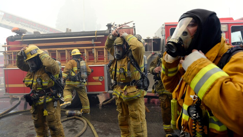 Los Angeles County firefighters battle a commercial fire in Hawthorne last week. A state audit found that only four of 622 fire captains in Los Angeles County were women.