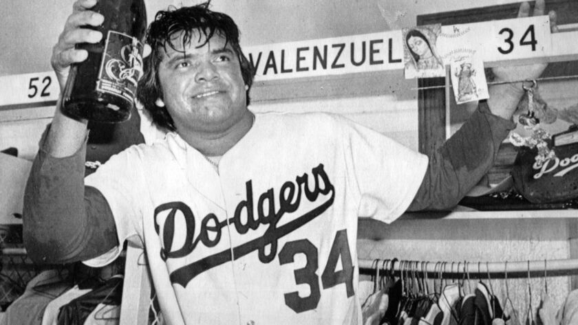 Dodger pitcher Fernando Valenzuela raises a magnum of champagne as the Dodgers toast their NL West v