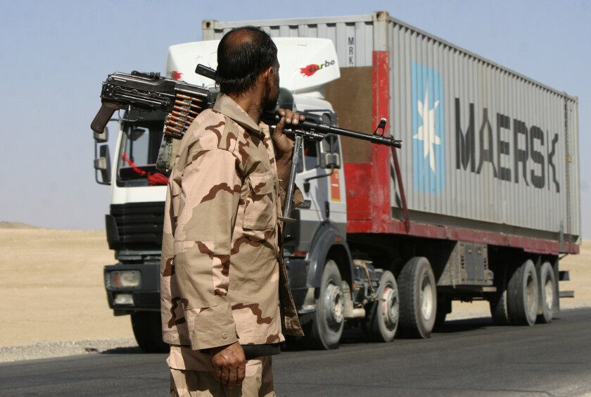 A private security contractor watches a NATO supply truck drive past south-west of Kabul, Afghanistan.