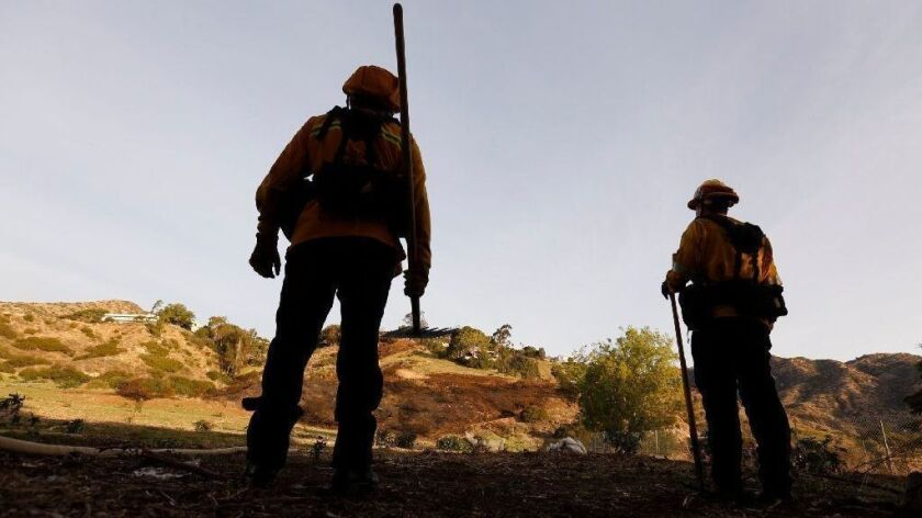Los Angeles County firefighters look for hot spots after putting out a Malibu brush fire in January.